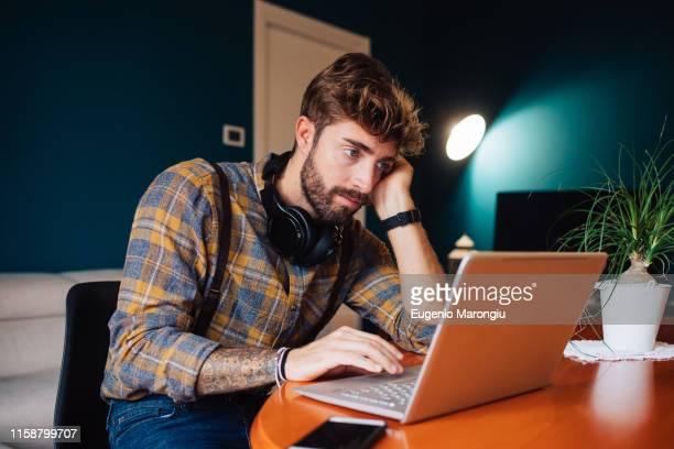 mid adult man sitting at living room table looking at laptop - starren stock-fotos und bilder
