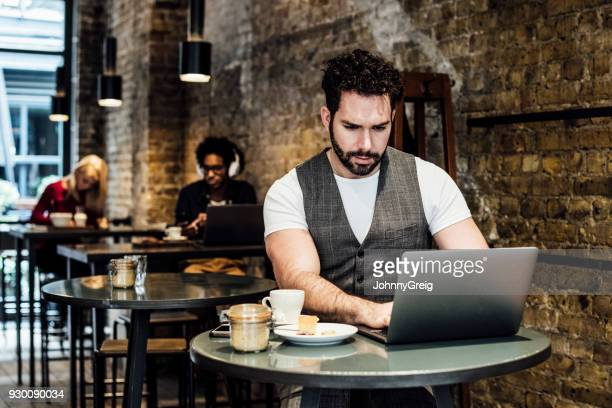 Mid adult man sitting at table in cafe and using laptop
