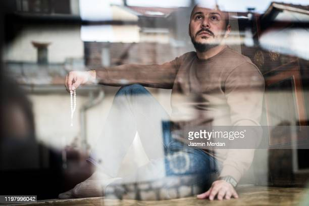 mid adult man sitting behind window - islam stock pictures, royalty-free photos & images