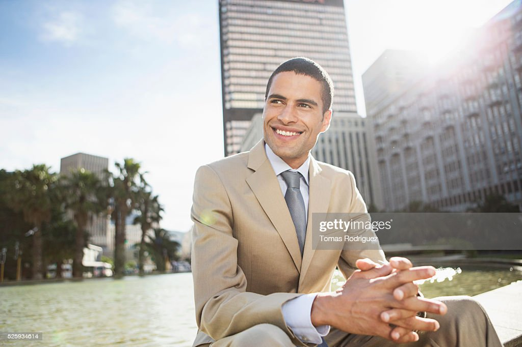 Mid adult man sitting by fountain : Stock Photo