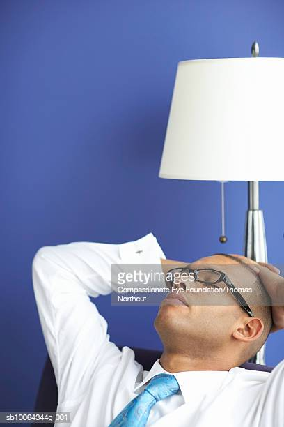 """mid adult man sitting in chair with hands behind head - """"compassionate eye"""" stock pictures, royalty-free photos & images"""