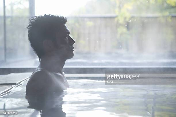 A Mid Adult Man Sitting in the Outdoor Hot Spring Bath, Side View