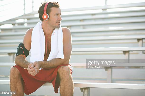 Mid adult man sitting on bench, taking a break from exercise, wearing headphones, towel around neck