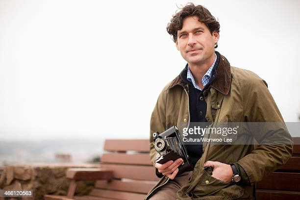 mid adult man sitting on bench with vintage camera, looking away - mid adult men stock pictures, royalty-free photos & images