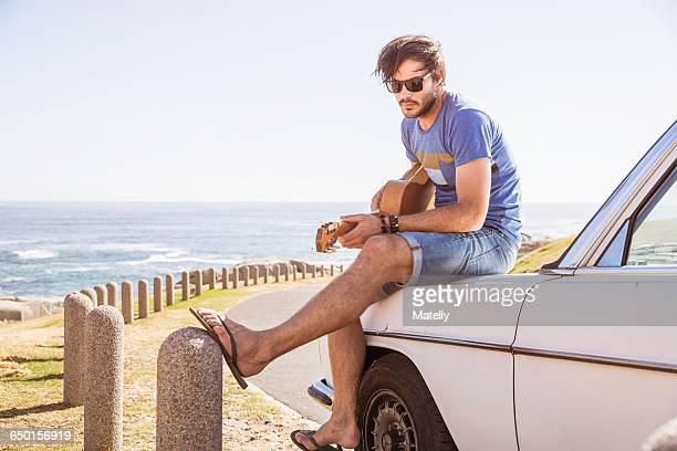 Mid adult man sitting on car at coast playing guitar, Cape Town, South Africa