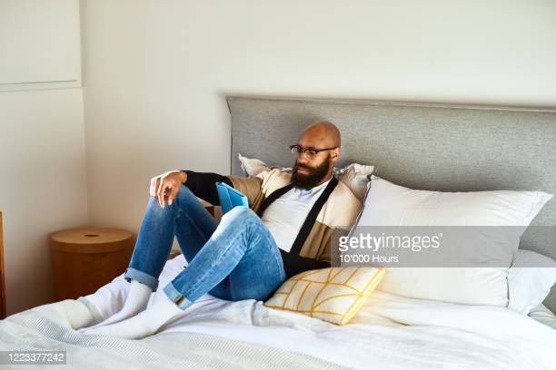 mid adult man sitting on ed reading tablet - hotel stock pictures, royalty-free photos & images