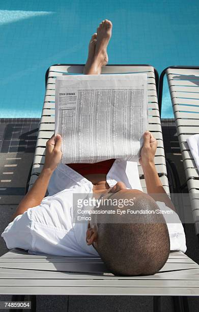 Mid adult man sitting on lounge chair at swimming pool, reading newspaper, elevated view