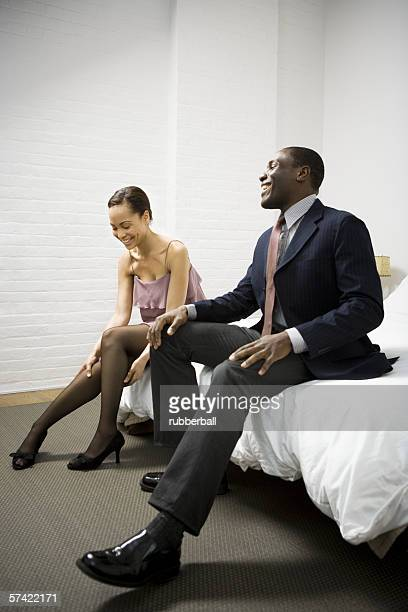Mid adult man sitting with a young woman and smiling