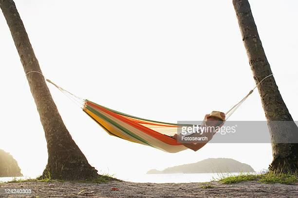 Mid adult man sleeping in hammock, St. John, US Virgin Islands, USA