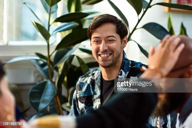mid adult man smiling in office team meeting - employee engagement stock pictures, royalty-free photos & images