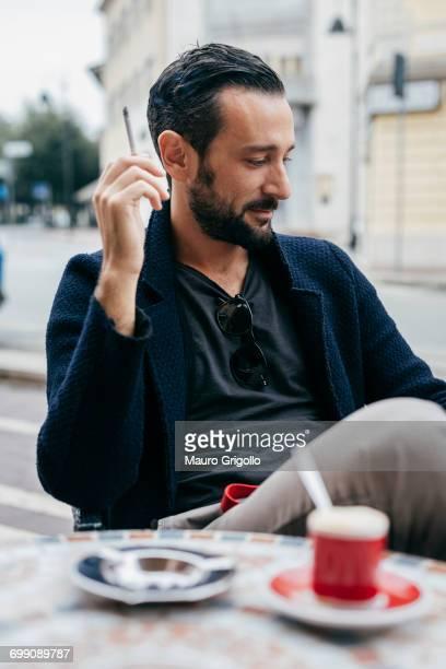 Mid adult man smoking cigarette at sidewalk cafe