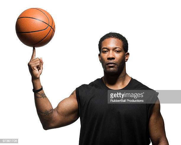 mid adult man spinning basketball in air, portrait - spinning stock pictures, royalty-free photos & images