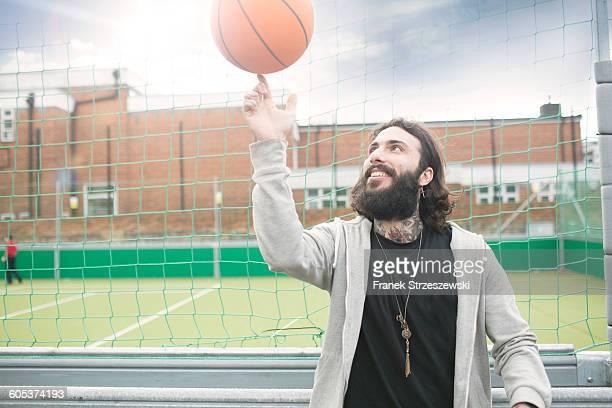 Mid adult man spinning basketball on finger