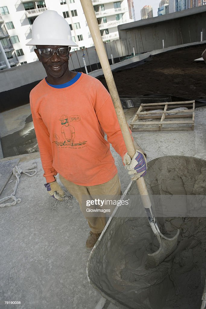 Mid adult man standing and holding a shovel : Foto de stock