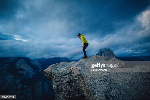 mid adult man standing at top of mountain peering over edge, yosemite national park, california, usa - 見渡す ストックフォトと画像
