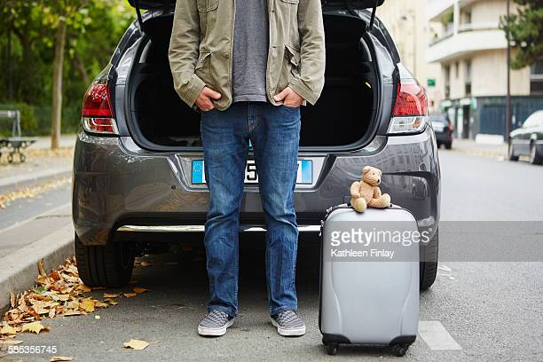 mid adult man standing beside car with open boot, suitcase in road - next to stock pictures, royalty-free photos & images