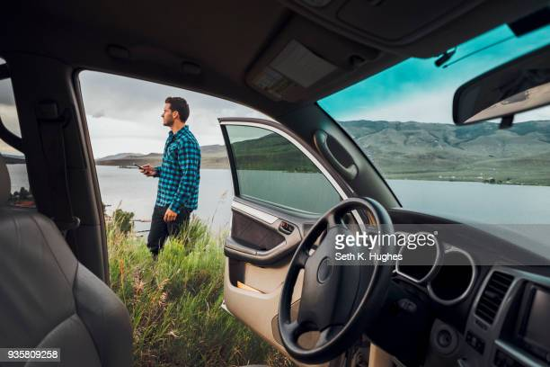 mid adult man standing beside dillon reservoir, holding smartphone, view through parked car, silverthorne, colorado, usa - car interior stock pictures, royalty-free photos & images
