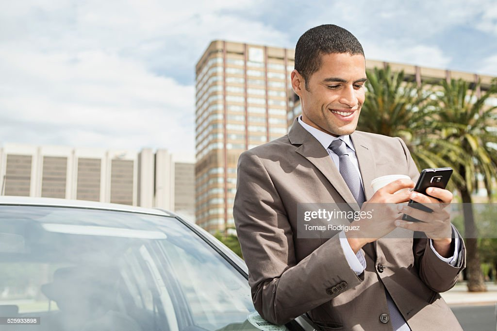 Mid adult man standing by car and using cell phone : Stock Photo