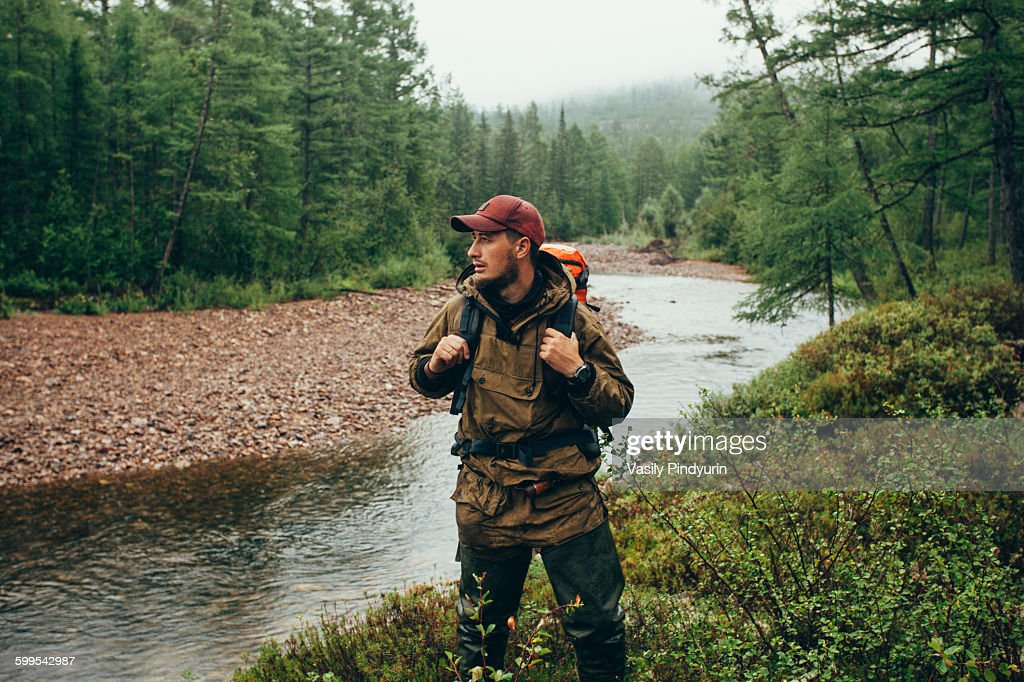 Mid adult man standing by river in forest : Foto de stock