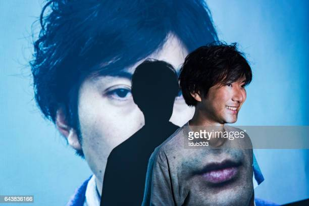 mid adult man standing in a projected image of himeself - projection equipment stock pictures, royalty-free photos & images