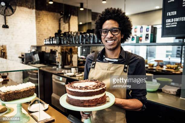 Mid adult man standing in cafe with chocolate cake on counter