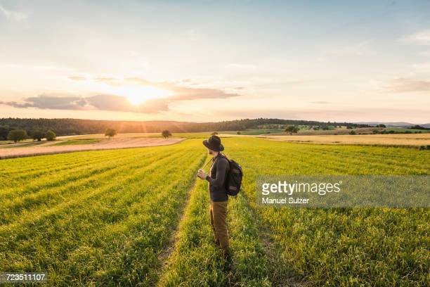 Mid adult man, standing in field, holding SLR camera, looking at view, Neulingen, Baden-Wrttemberg, Germany