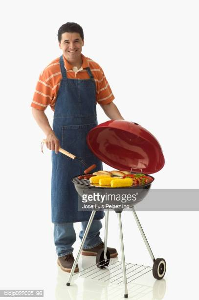 Mid adult man standing in front of a barbecue grill