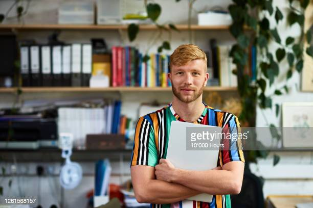 mid adult man standing in office, looking at camera - office stock pictures, royalty-free photos & images