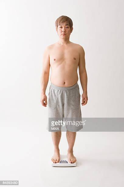 Mid adult man standing on bathroom scale