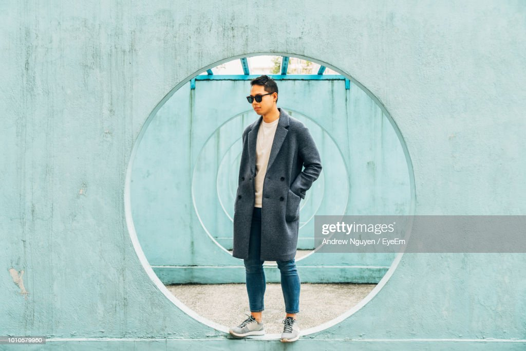 Mid Adult Man Standing On Hole In Wall : Stock Photo