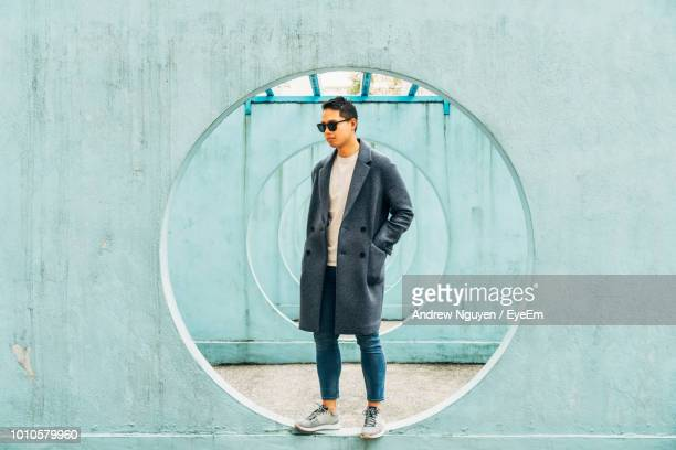 mid adult man standing on hole in wall - fashion hong kong stock photos and pictures