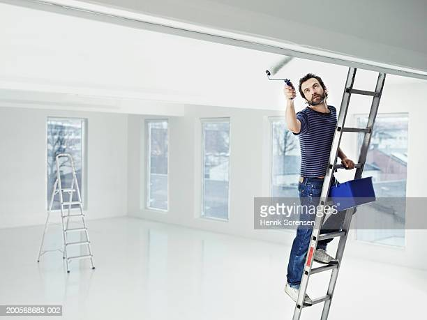 Mid adult man standing on ladder painting apartment