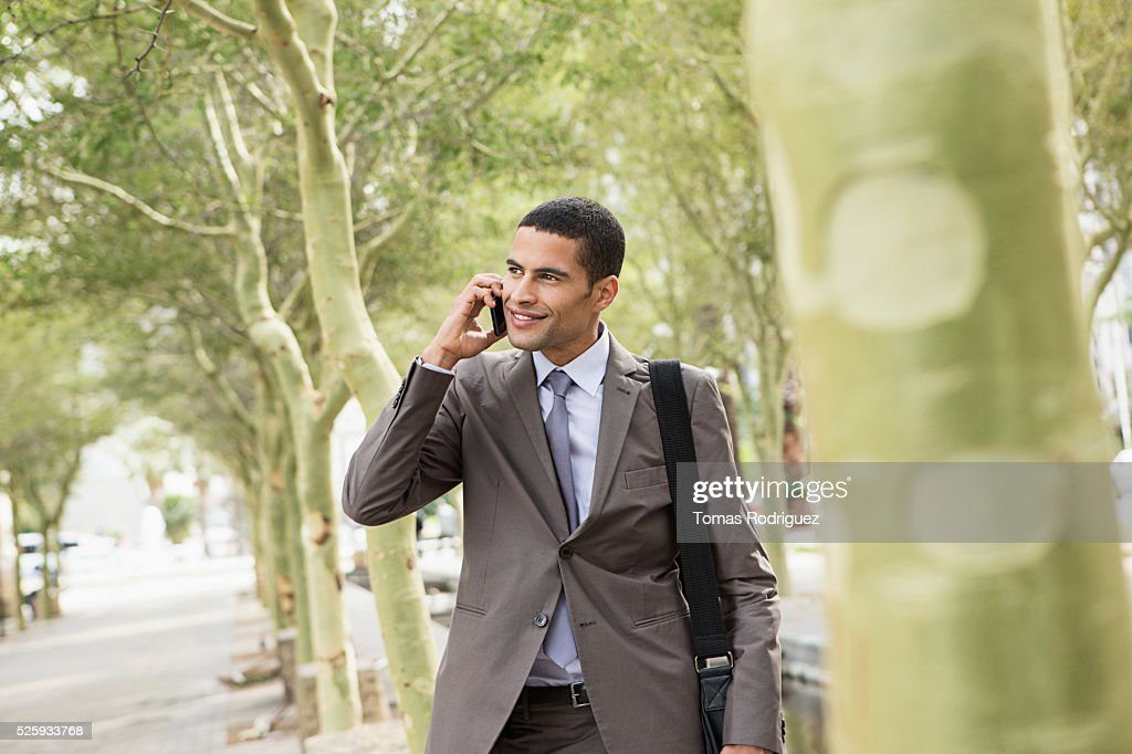 Mid adult man standing on pavement and talking on cell phone : Stockfoto