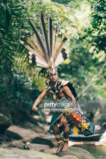 mid adult man standing on rock wearing costume by river in forest - central kalimantan stock pictures, royalty-free photos & images