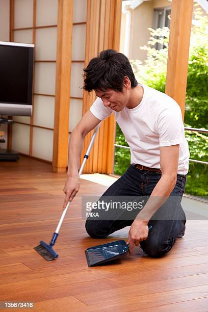 Mid adult man sweeping floor with broom and dustpan