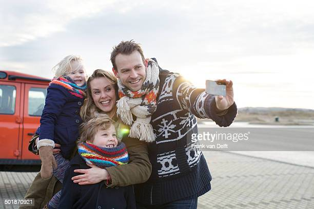 mid adult man taking a family selfie in coastal parking lot - four people in car stock pictures, royalty-free photos & images