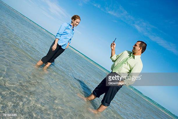 Mid adult man taking a photograph of a mid adult woman on the beach