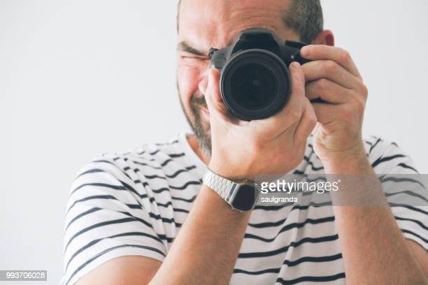 Mid adult man taking a picture with a reflex camera