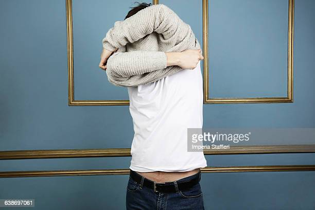 mid adult man taking off jumper - mid volwassen mannen stockfoto's en -beelden