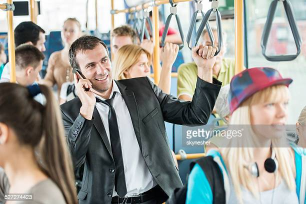 Mid adult man talking on phone while commuting by bus.