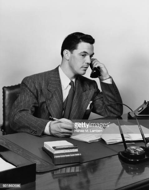 Mid adult man talking on telephone in office