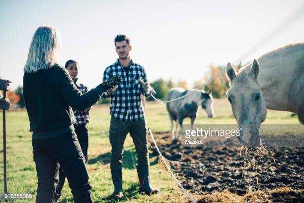 Mid adult man talking with instructor by horse at organic farm
