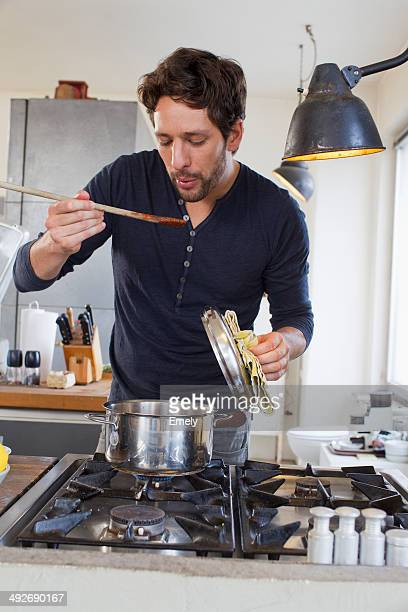 Mid adult man tasting food from wooden spoon in kitchen