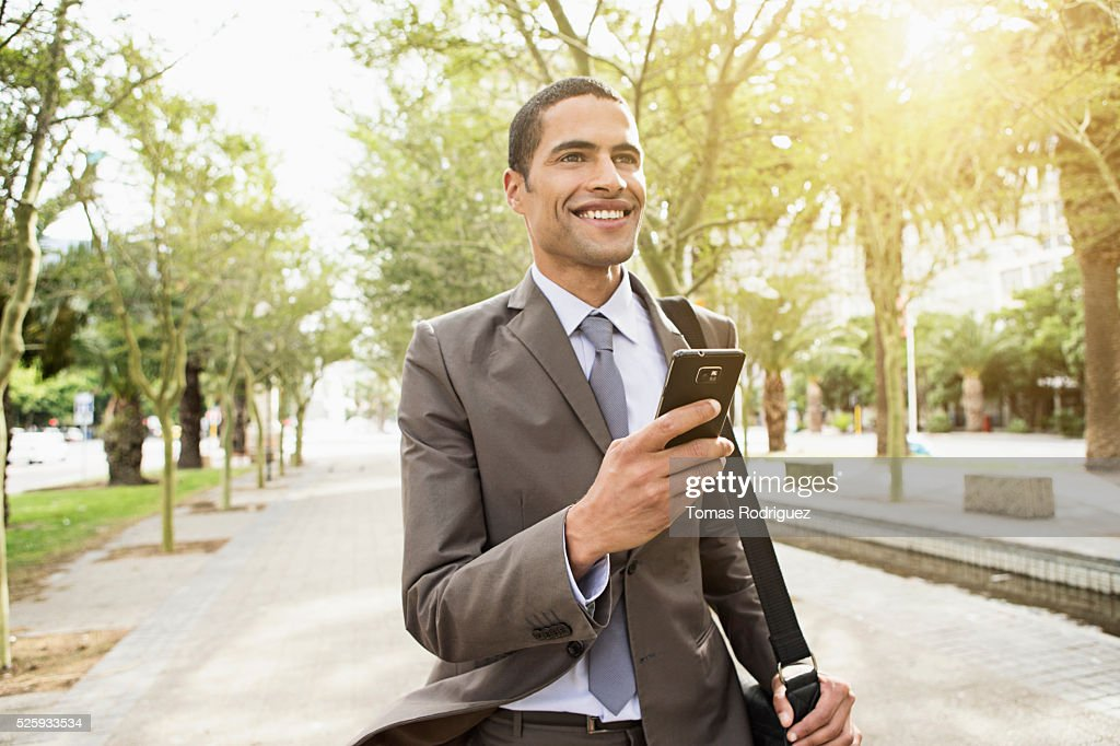 Mid adult man text messaging while walking along pavement : Stockfoto