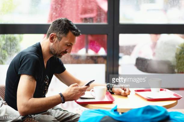 mid adult man texting  in cafe - michael turk stock pictures, royalty-free photos & images