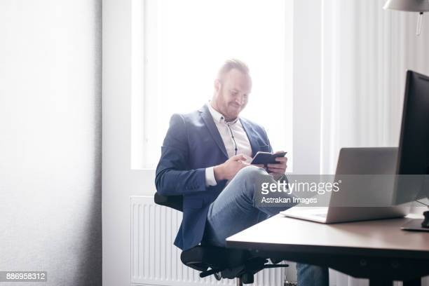 Mid adult man texting on smart phone and smiling