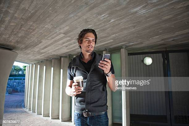 Mid adult man texting on smartphone in city underpass
