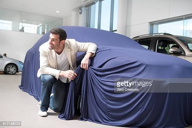 Mid adult man uncovering and peeking at new car in car dealership