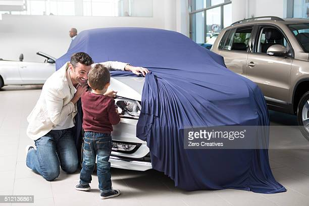 Mid adult man uncovering new car for son in car dealership