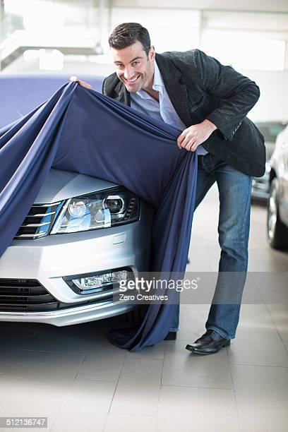Mid adult man uncovering new car in car dealership